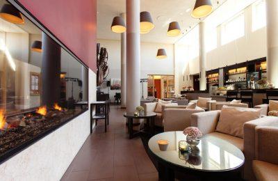 Stilvolle Bar mit Kamin und ockerfarbenden Sesseln
