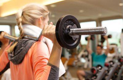 Frau trainiert mit SZ-Stange im Fitnesscenter