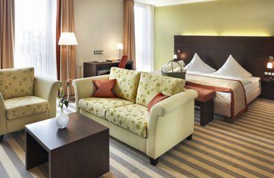 Bett und Wohnraum mit Sofas im Doppelzimmer im Lichtflügel
