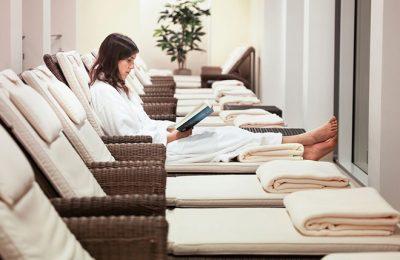 Frau in weißem Bademantel liest Buch im Ruhebereich