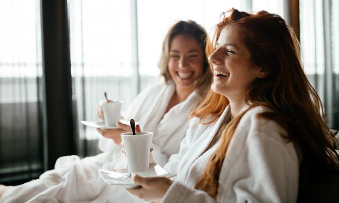 Zwei junge Frauen in weißen Bademänteln entspannen im Spa