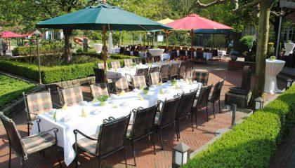 Zahlreiche Tische und Stühle unter Sonnenschirmen im Schlimmergarten