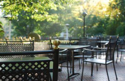 Schwarze Tische und Sitzgelegenheiten bei Sonnenschein im Garten
