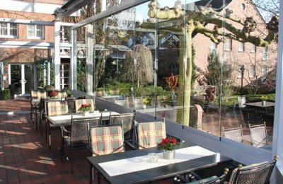 Tische vor Glaspanorama im Wintergarten