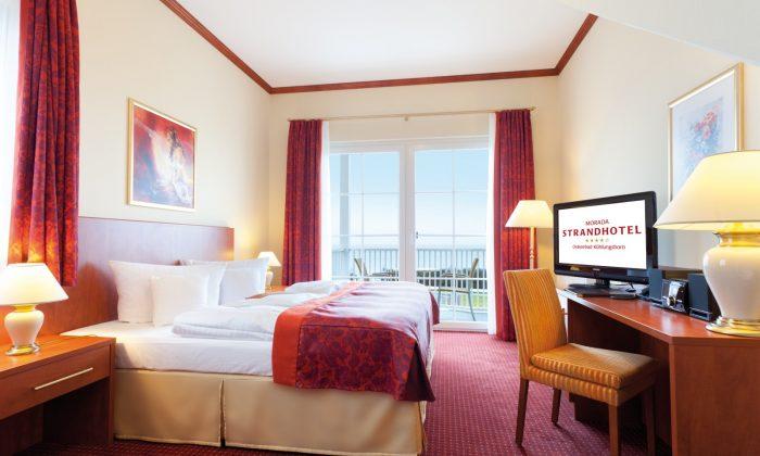Bett und Wohnraum in der Turmsuite mit Blick aufs Meer