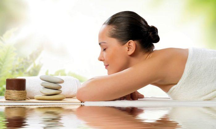 Frau in weißem Handtuch genießt Massage