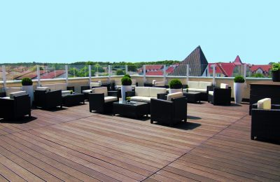 Zahlreiche Sitz- und Ecksofas auf der Dachterrasse vor blauem Himmel