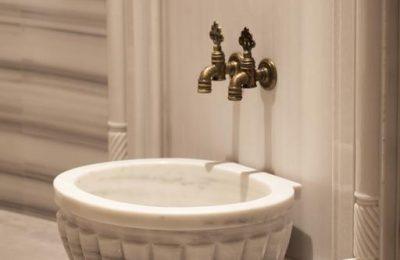 Weißer Trinkbrunnen mit zwei Wasserhähnen