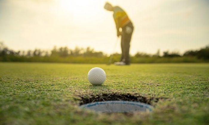Mann spielt Golf bei Sonnenuntergang
